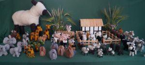 udsnit af udstilling med bondehus i baggrunden, hunde i forgrunden. får i indhegningen. buket med korn ved siden af huset.